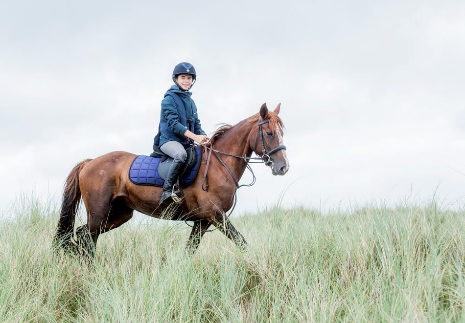 young woman ridding horse in ireland